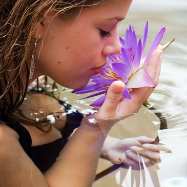 woman smelling water lilly at freestyle resort port douglas